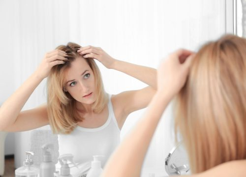 Woman inspecting her scalp for psoriasis