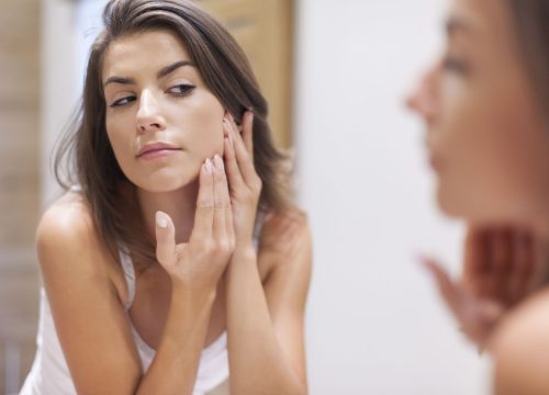 Woman looking at her acne in the mirror