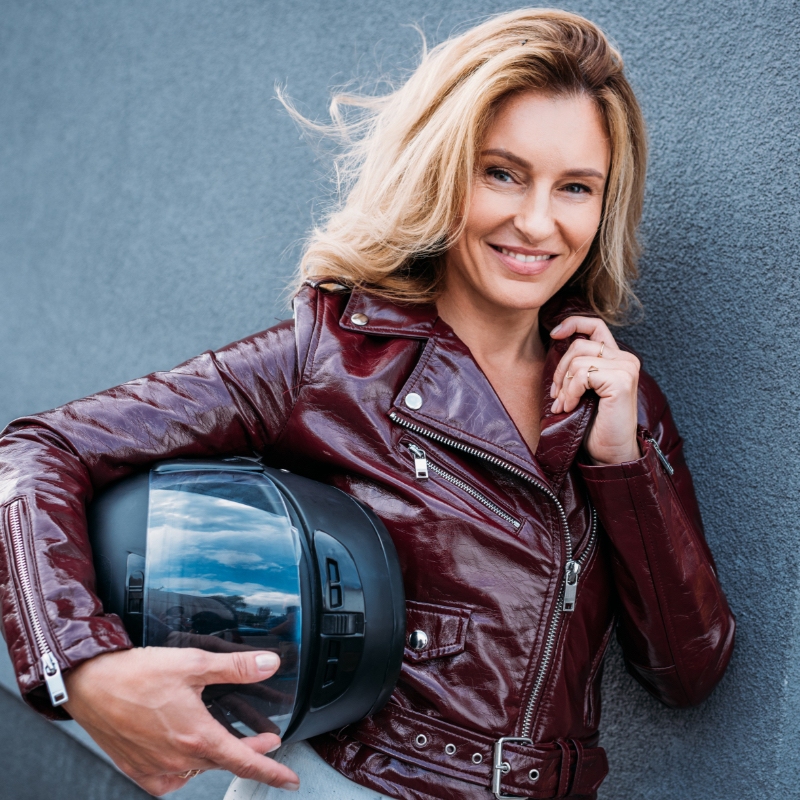 Woman in leather jacket holding a motorcycle helmet