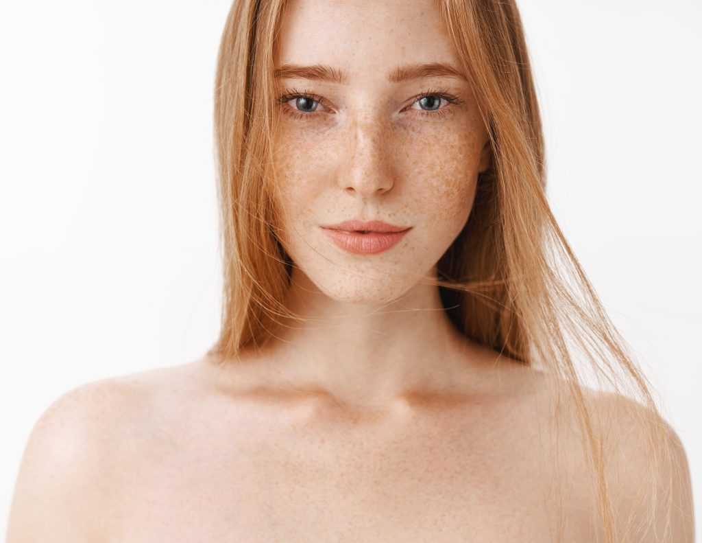 Close-up shot of attractive feminine naked redhead woman with freckles posing over gray background sensualy with sexy look in eyes standing daring having confidence in own body.