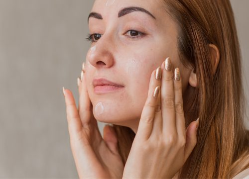 Woman with rosacea applying lotion to her face